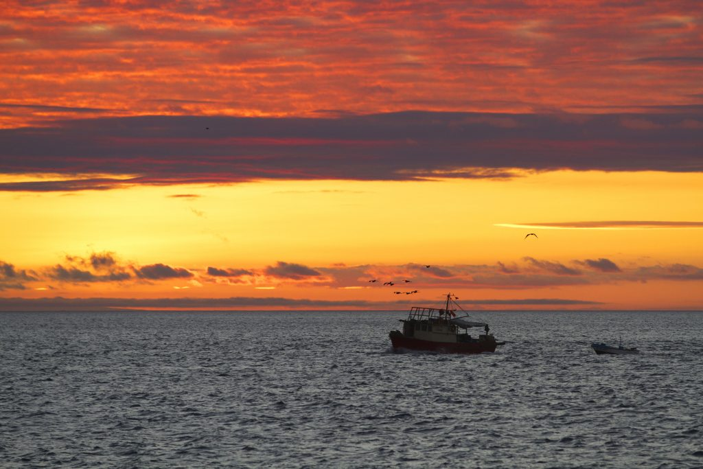 a stunning sunset blankets the horizon with a small fishing boat in the foreground