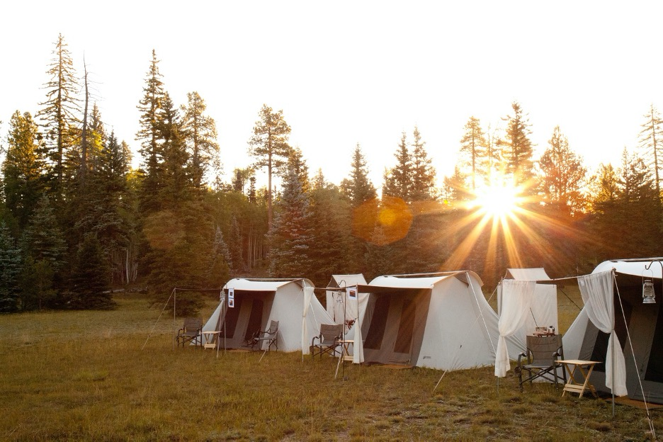canvas tents sit in front of a forest with a sunrise behind them
