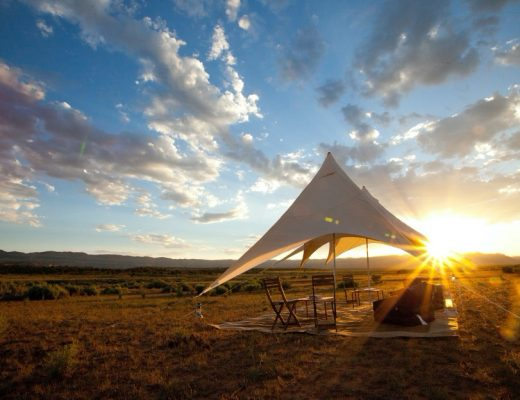a canvas tent sits in the desert with sun setting