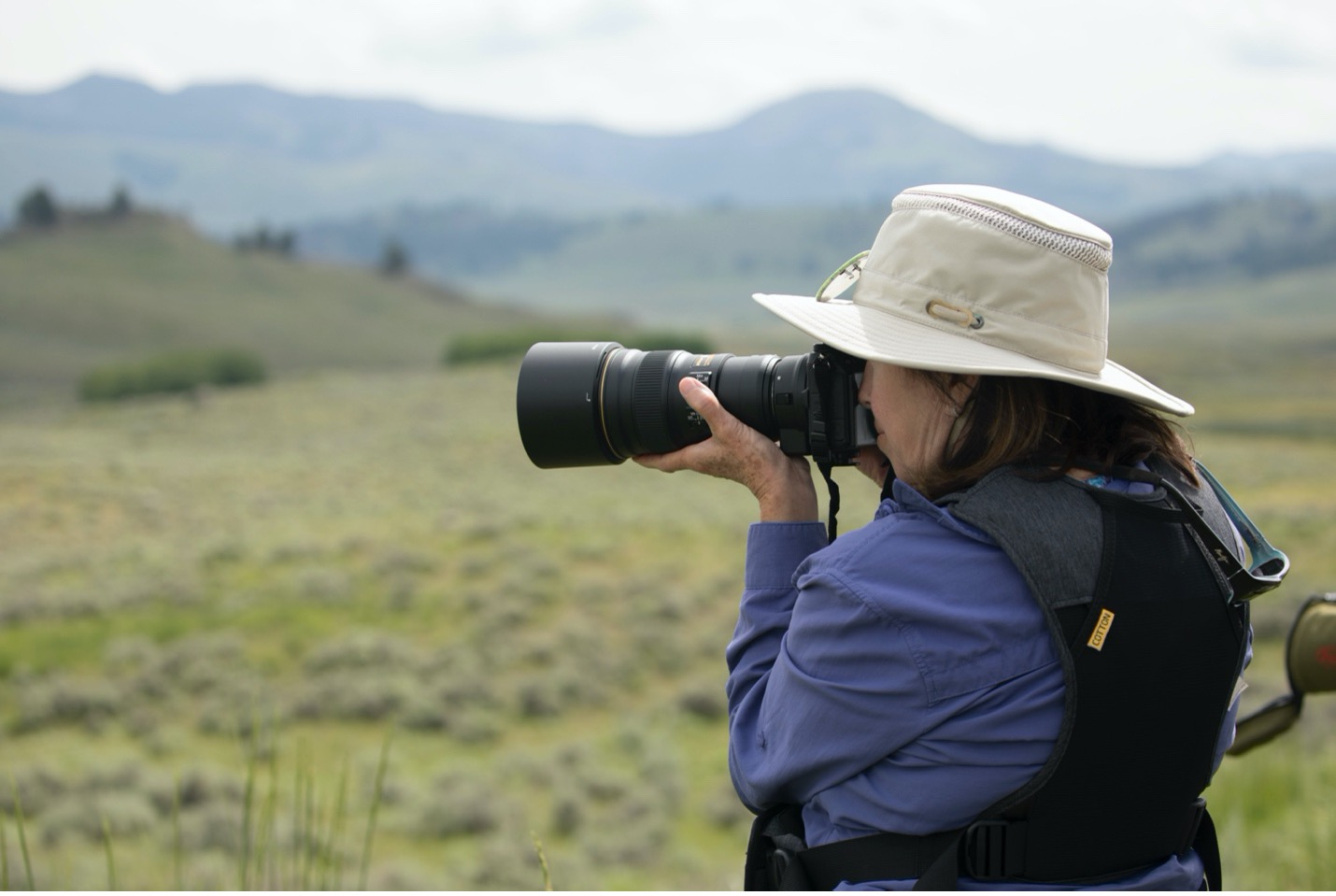 a woman photographs with a telephoto lens in Yellowstone National Park