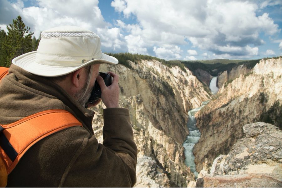 a man photographs the grand canyon of yellowstone falls